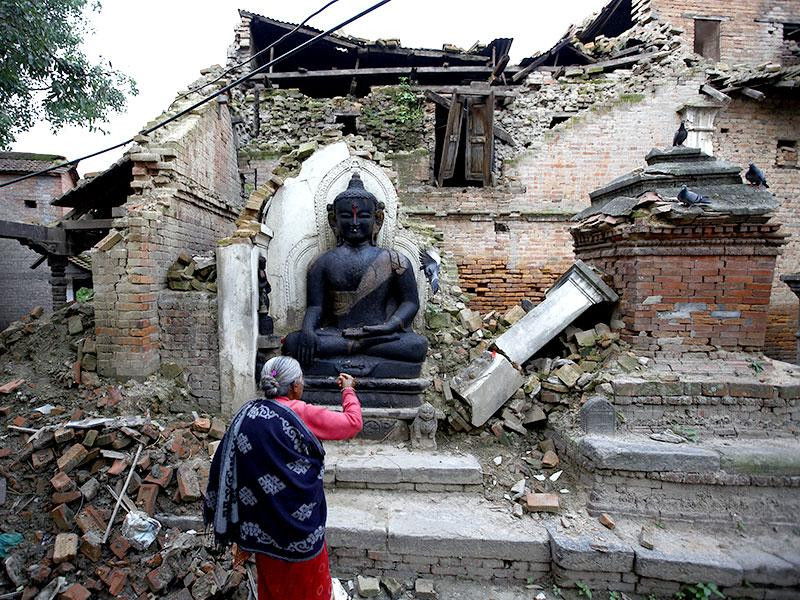 A woman offers daily prayers at the statue of Lord Buddha that was damaged during the earthquake in Bhaktapur. Earthquake survivors in Nepal are still in a dire need for food, shelter and clean water. (Reuters Photo)