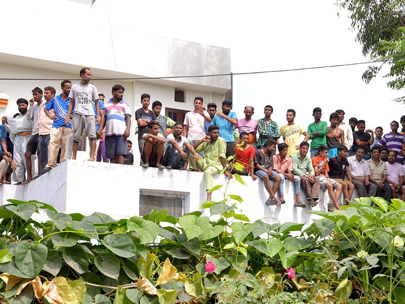 Residents watch as security forces battle armed attackers at the police station in Dinanagar town, in the Gurdaspur district of Punjab. (AFP Photo)