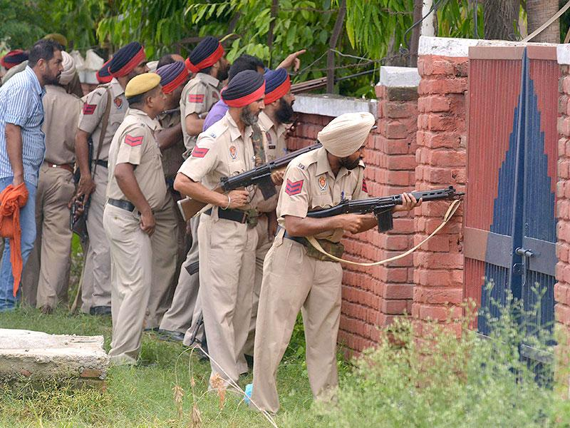 Punjab police personnel take position during an encounter with armed attackers at the police station in Dinanagar town in Gurdaspur district. (AFP Photo)
