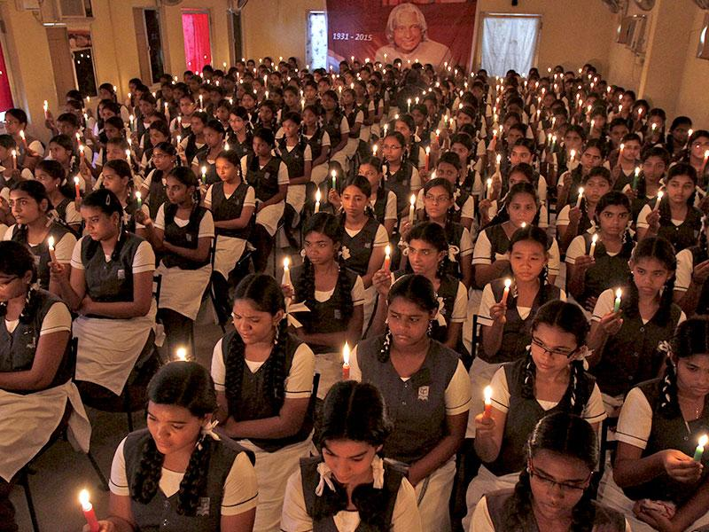 School girls hold candles as they sit in front of a portrait of former Indian president APJ Abdul Kalam during a prayer ceremony in Chennai. (Reuters Photo)