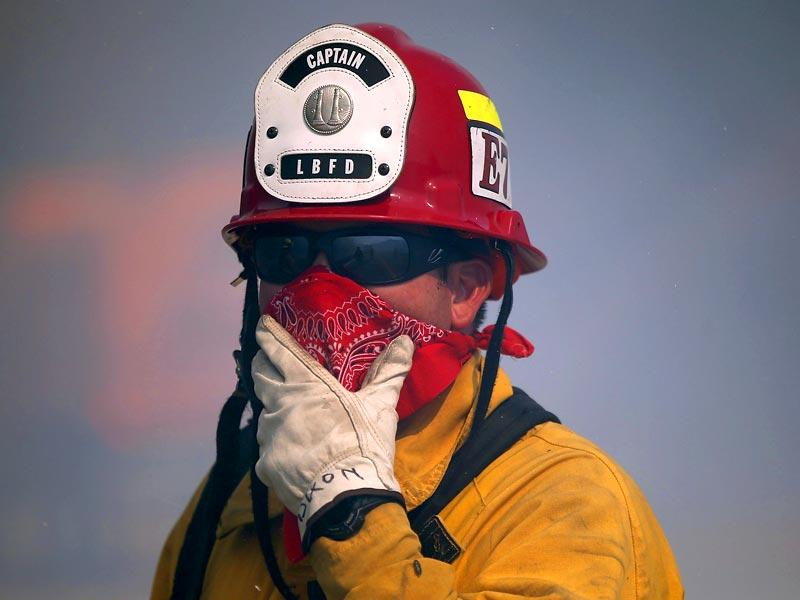 A Long Beach firefighter shields his face from smoke as he mops up hot spots after the Rocky Fire burned a hillside in Lower Lake, California. (AFP Photo)