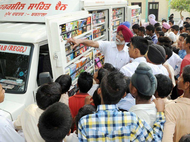 Slaying sorcery with science, Tarksheel Society member Rajinder Singh Bhadaur guides children gathered around a mobile library to a book, at Government Boys School, Lehragaga, in Sangrur district; and (below) his colleague, Jasvir Soni, explaining a common trick at DAV School, Lehragaga. Bharat Bhushan/HT