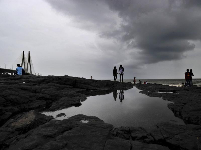 Dark clouds loom over the city as people take a stroll at Bandra, in Mumbai. (Vidya Subramanian/HT photo)