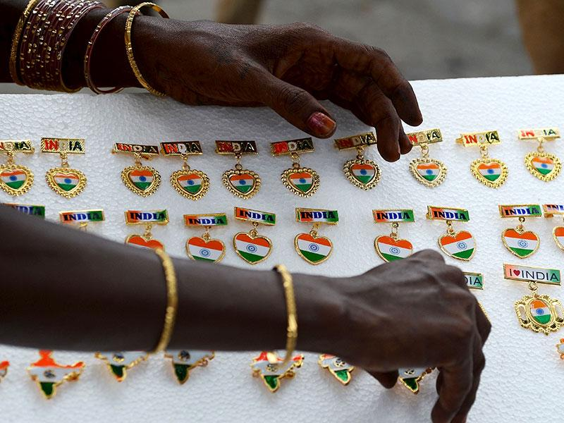 A woman arranges pins displaying the colours of the national flag as she waits for customers at a stall (AFP Photo)