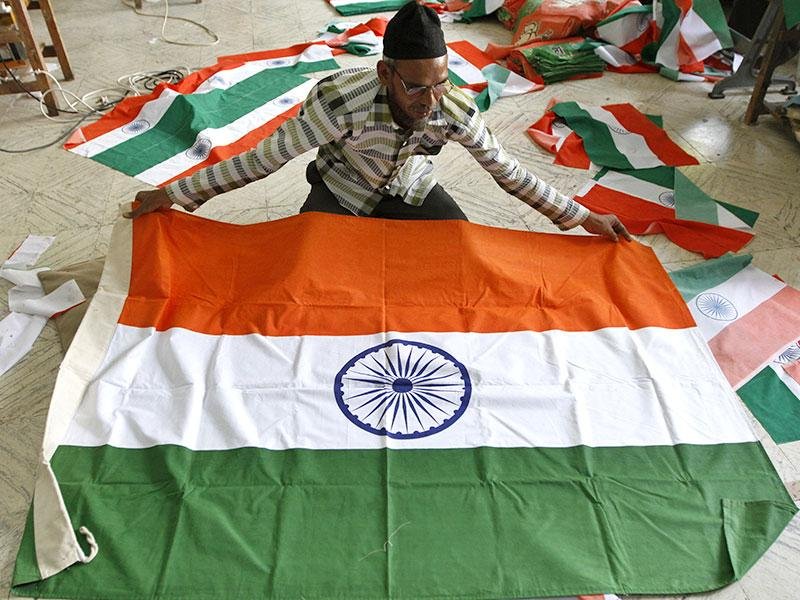 A man prepares to fold an Indian flag being made at a factory ahead of Independence Day in Ahmadabad (AP Photo)