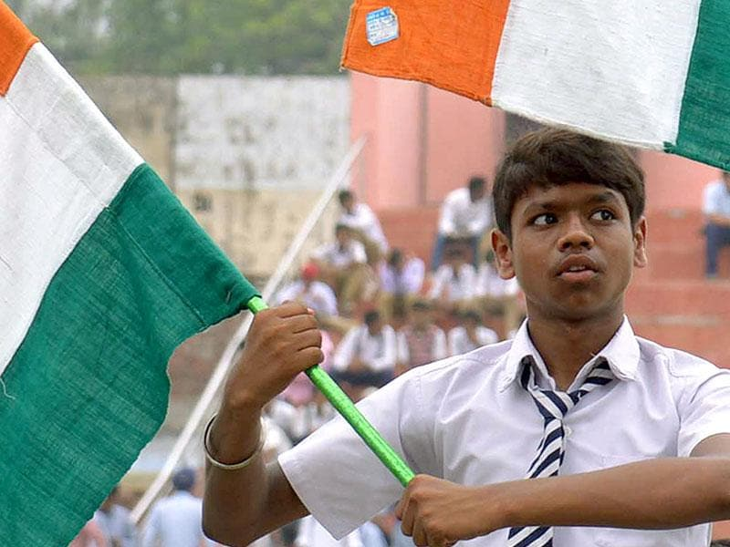 A schoolboy holds the tricolour during a rehearsal for Independence Day Parade celebrations (AFP Photo)