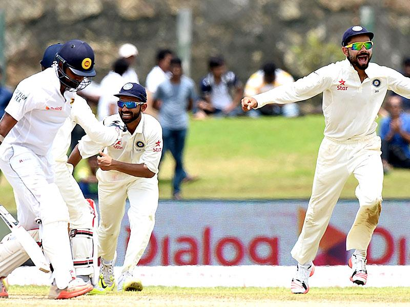 Kohli, second from right, and Ajinkya Rahane, second from left, celebrate the dismissal of Sri Lankan batsman Lahiru Thirimanne, left, during the first day of the first Test. (AFP Photo)