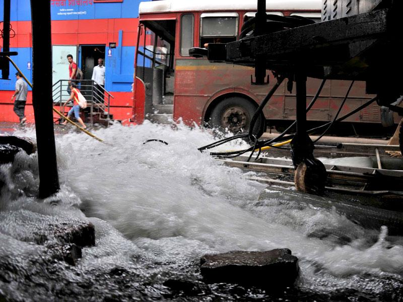 BMC workers repair a water pipeline after it burst at Dadar, in Mumbai. (Photo credit: Bhushan Koyande)