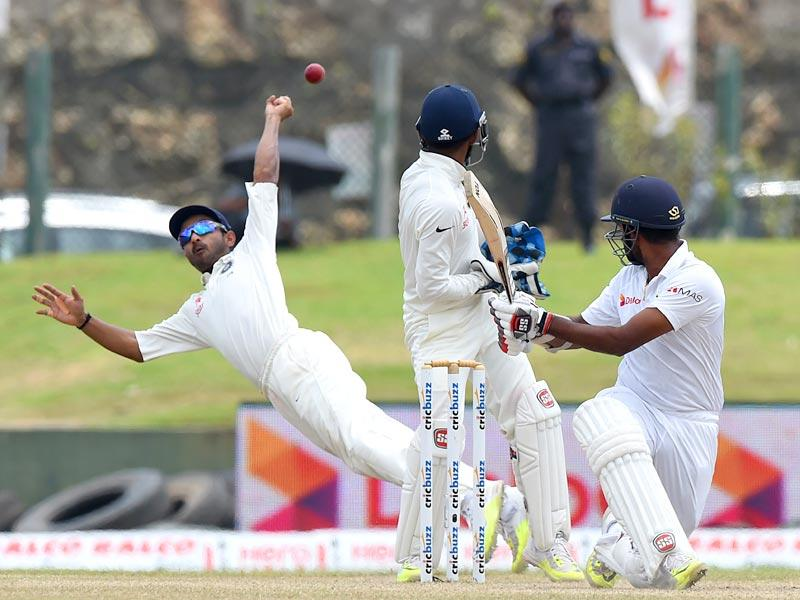 Rahane, left, misses a catch off the batting of Lahiru Thirimanne, right, as Wriddhiman Saha looks on. (AFP Photo)