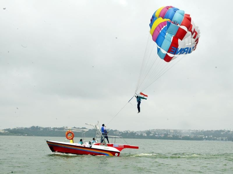 To make the most of the pleasant weather ahead of the Independence Day, a youth enjoys water parasailing holding a national flag at Boat Club in Bhopal. (HT Photo/Praveen Bajpai)