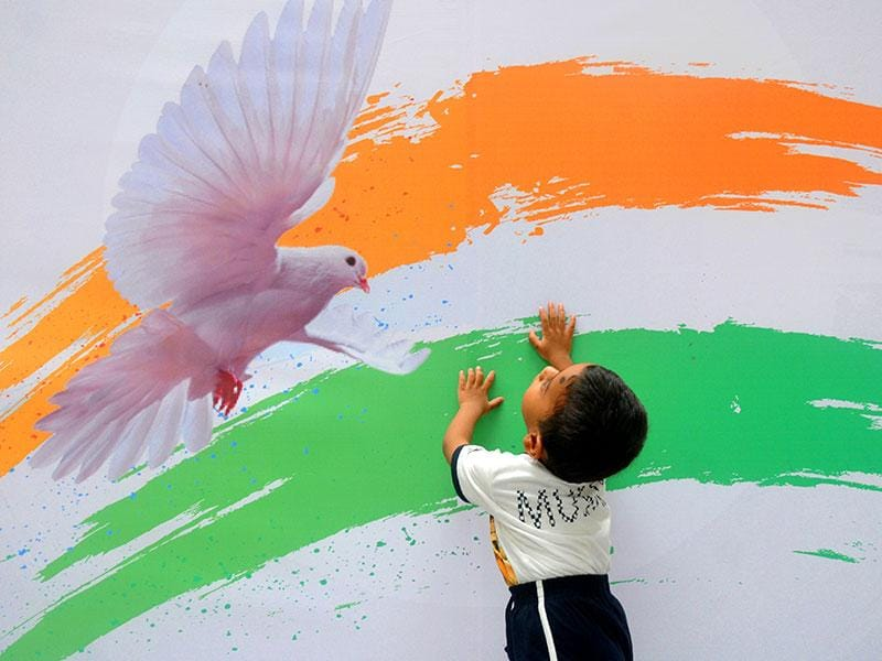 A kid plays against the backdrop of the Indian Tricolour on Independence Day at Goregoan, in Mumbai. (Photo: Sanjay Solanki)