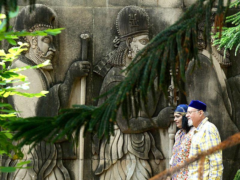 A Parsi couple walks past relief figures of knights at a Fire Temple. (AFP Photo)
