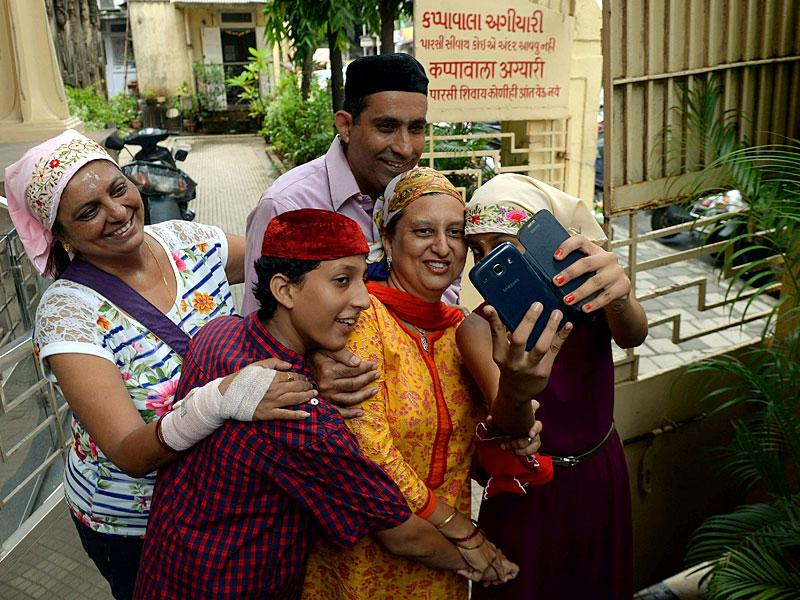 A Parsi family takes a photograph on their mobile phones outside the Fire Temple after offering prayers on 'Navroz' in Mumbai. (AFP Photo)