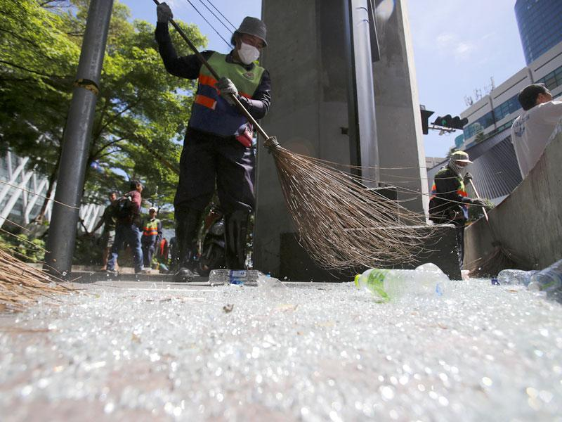 Workers sweep broken glass near the Erawan Shrine at Rajprasong intersection in Bangkok, Thailand, Tuesday, Aug. 18, 2015, the morning after an explosion. Police combed through shattered glass and other debris Tuesday from a bomb blast in central Bangkok, trying to determine who set off the most devastating single attack in the capital's recent history. (AP Photo/Sakchai Lalit)