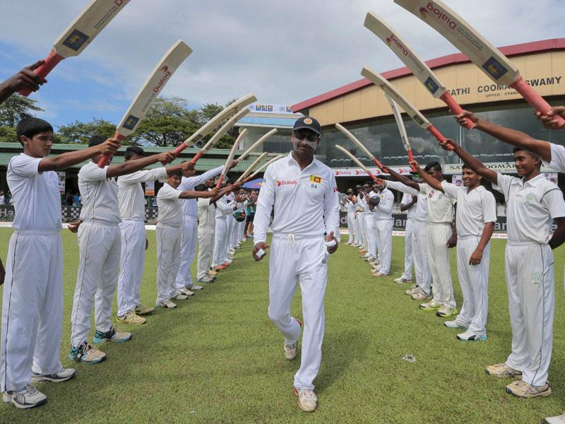 Sri Lanka's Kumar Sangakkara, centre, is greeted with an arch of cricket bats as he enters the field for the last match of his Test career, Day 1 of the second Test against India in Colombo, Sri Lanka, on August 20, 2015. (AP Photo)