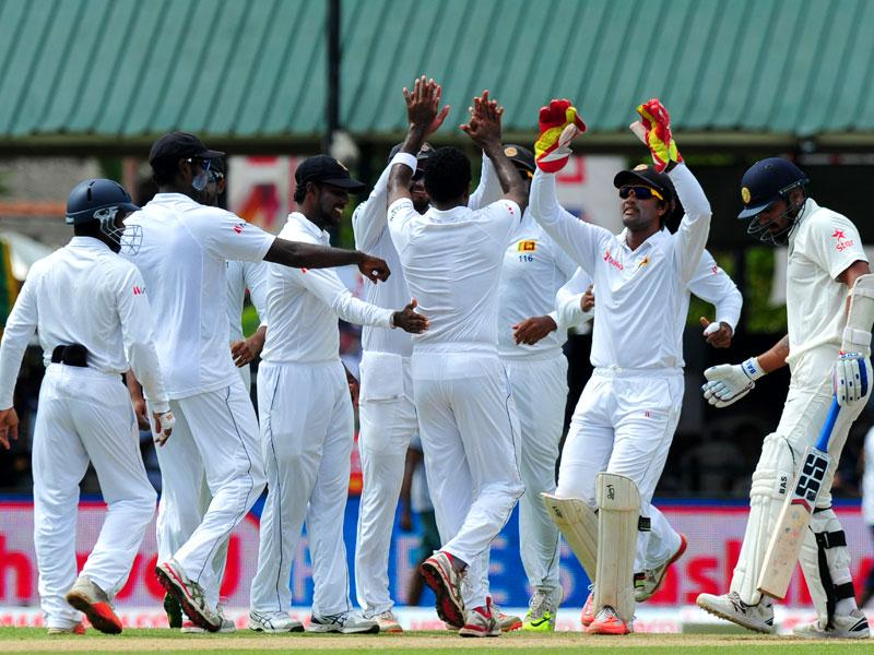 Sri Lankan bowler Dhammika Prasad (C) celebrates with teammates after the dismissal of Indian opener Murali Vijay (R) on Day 1 of the second Test match against India at the P Sara Oval Stadium in Colombo. (AFP Photo)