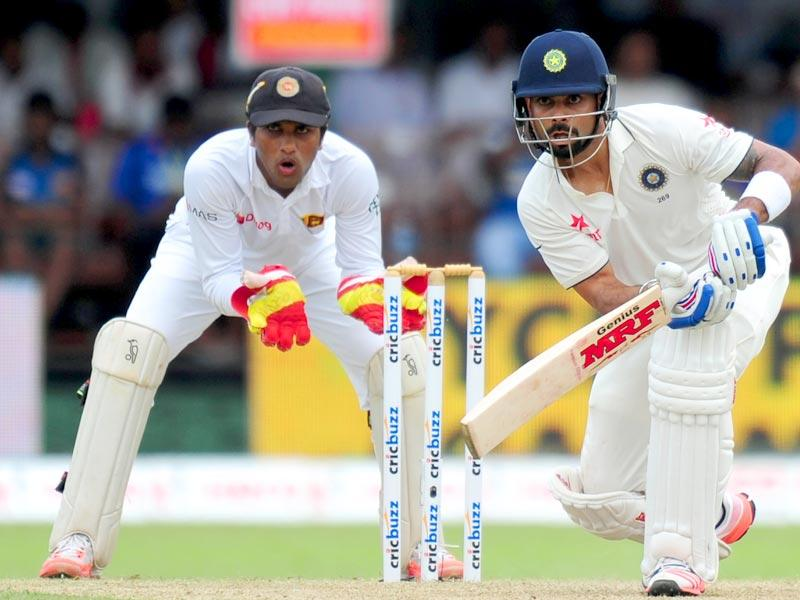 Indian cricket captain Virat Kohli (R) plays a shot as Sri Lankan wicketkeeper Dinesh Chandimal looks on during the opening day of their second test match between Sri Lanka and India at the P Sara Oval Cricket Stadium in Colombo. (AFP Photo)