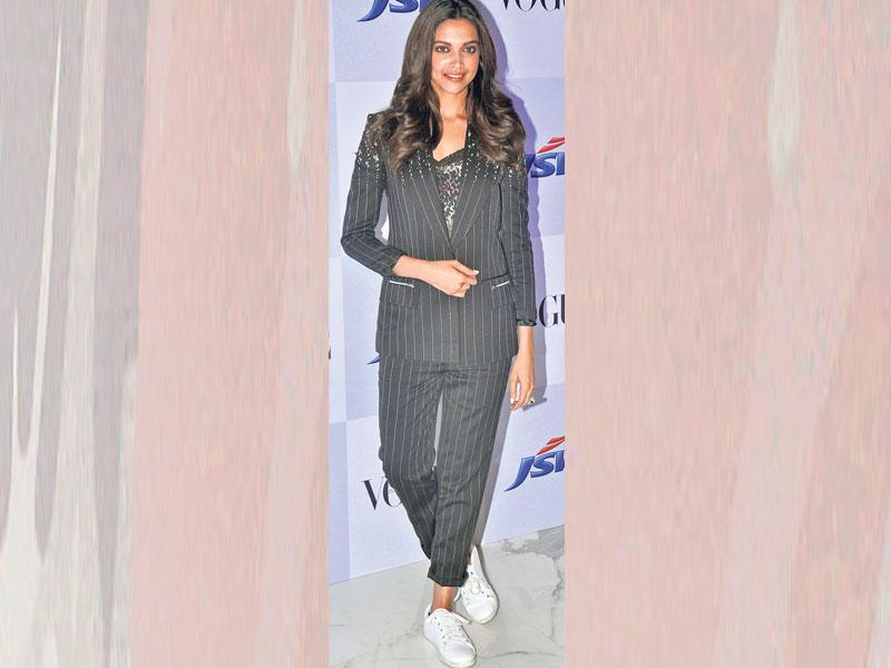 Actor Deepika Padukone looks hot in her striped pantsuit. Cutting the formalness of a pantsuit, she rocks the athleisure trend by wearing white sports shoes.
