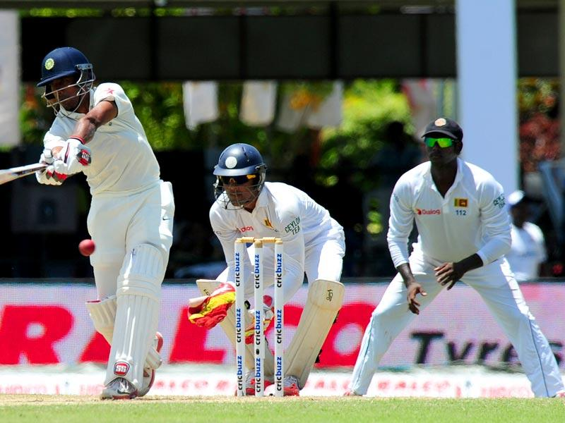 India's Wriddhiman Saha (L) plays a shot as Sri Lankan wicketkeeper Dinesh Chandimal (C) and captain Angelo Mathews (R) look on. (AFP Photo)