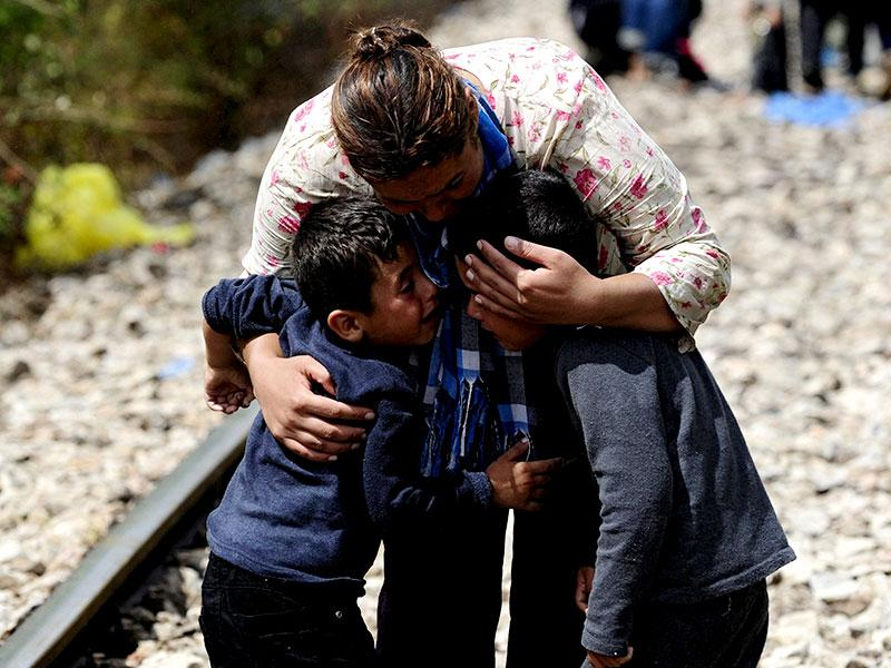 A woman hugs two boys after crossing Greece's border into Macedonia. (Reuters Photo)