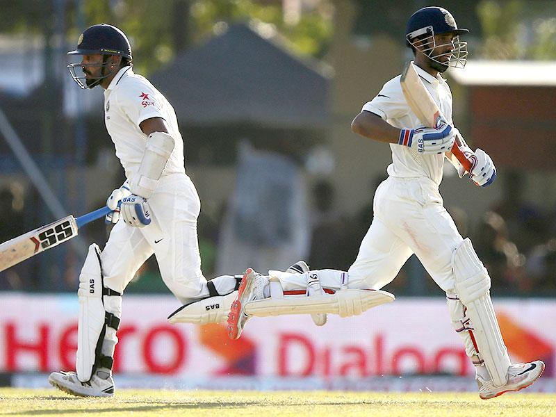 Ajinkya Rahane (R) and Murali Vijay run between wickets during the third day of their second test cricket match against Sri Lanka in Colombo. REUTERS/Dinuka Liyanawatte