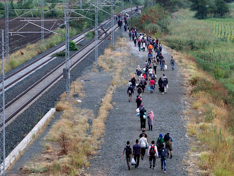 Migrants walk along the railway tracks at the Greek-Macedonian border, blocked by Macedonian police near the town of Idomeni, Northern Greece. (AFP Photo)
