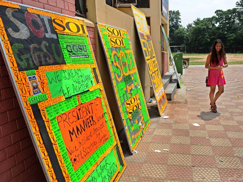 A student walk past a board with election posters all over it, at SD College, Sector 32 on Friday. Gurminder Singh/HT