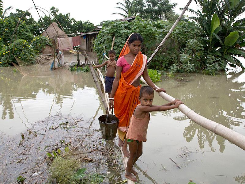 Locals affected by monsoon rains walk through a makeshift bridge in Mayong village, about 55 kilometers (34 miles) east of Guwahati. The flooding in India's northeastern Assam state is the worst in the past three years, affecting nearly 600,000 people in 19 of the state's 27 districts, officials said. (AP Photo/Anupam Nath)
