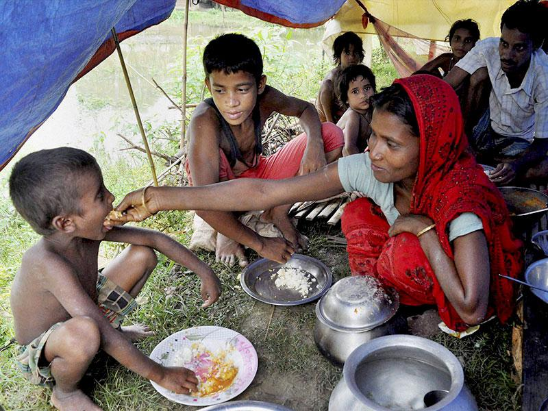 A mother feeds her children at a relief camp after the family's home was submerged in floods in Bura Bure area of Morigaon district of Assam. (PTI Photo)
