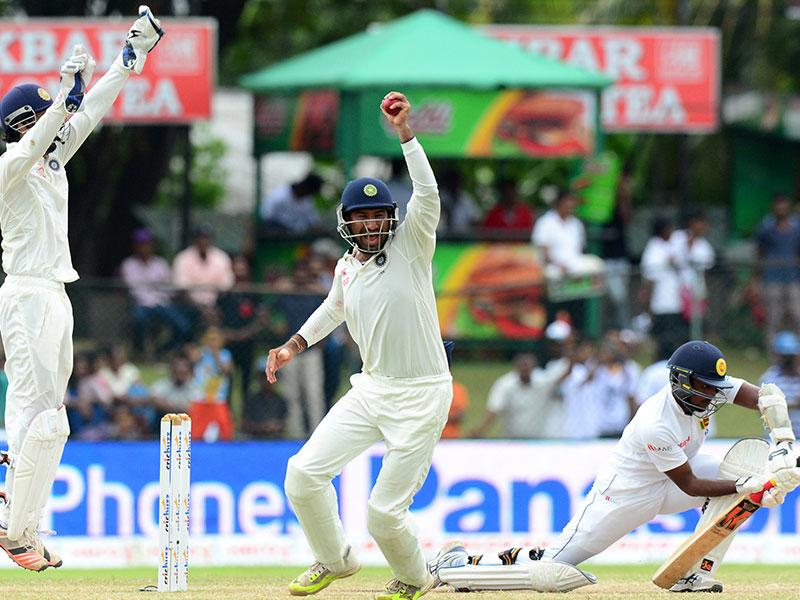 India's Stuart Binny, centre, takes a catch to dismiss Sri Lanka's Tharindu Kaushal, right, on Day 5 of the second Test match at the P Sara Oval in Colombo. (AFP Photo)
