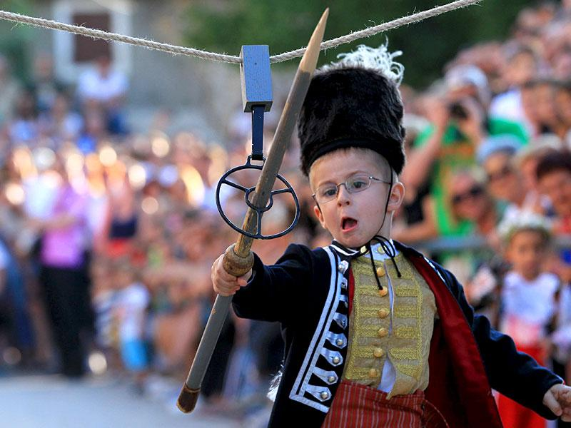 A child runs during the Children's Alka competition on August 23, 2015. The event commemorates Croatia's victory over the Ottomans. (Reuters)