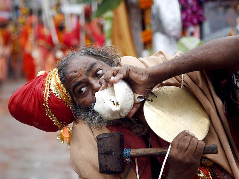 A Sadhu, or Hindu holy man, blows a conch or horn as he participates in a procession during Kumbh Mela, or Pitcher festival, at Trimbakeshwar in Nashik. (AP Photo)