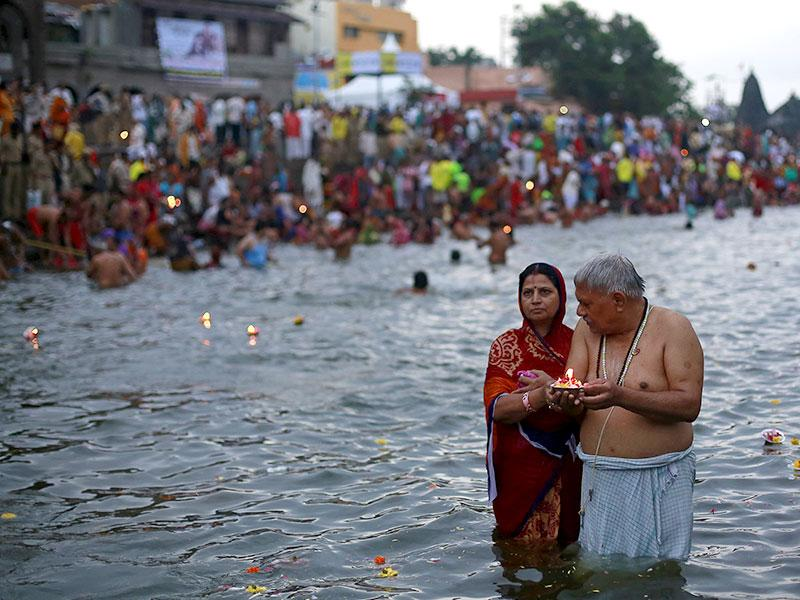 Hindu devotees pray while standing in the Godavari river during Kumbh Mela.