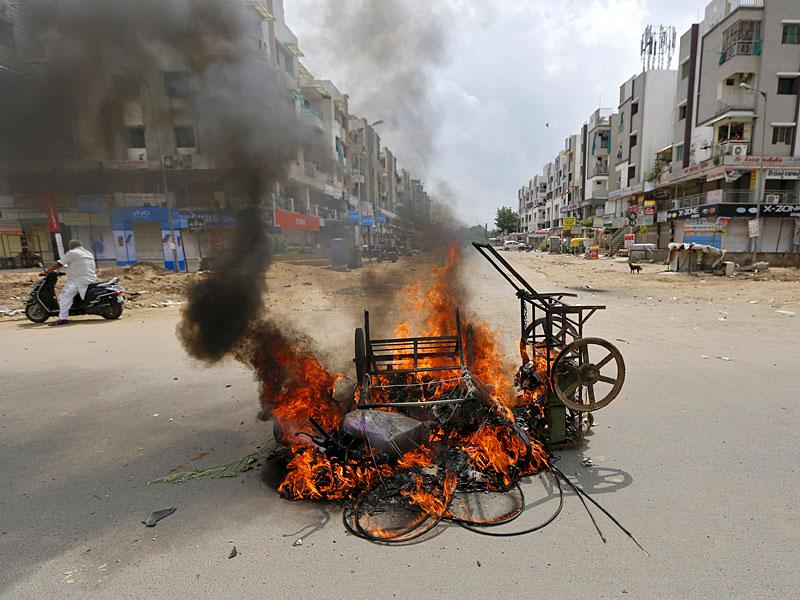 A man on a scooter stands next to burning vehicles after clashes between forces and protesters in Ahmedabad. The Patel community, led by Hardik Patel, has been demanding reservation for the powerful community. (Reuters Photo)
