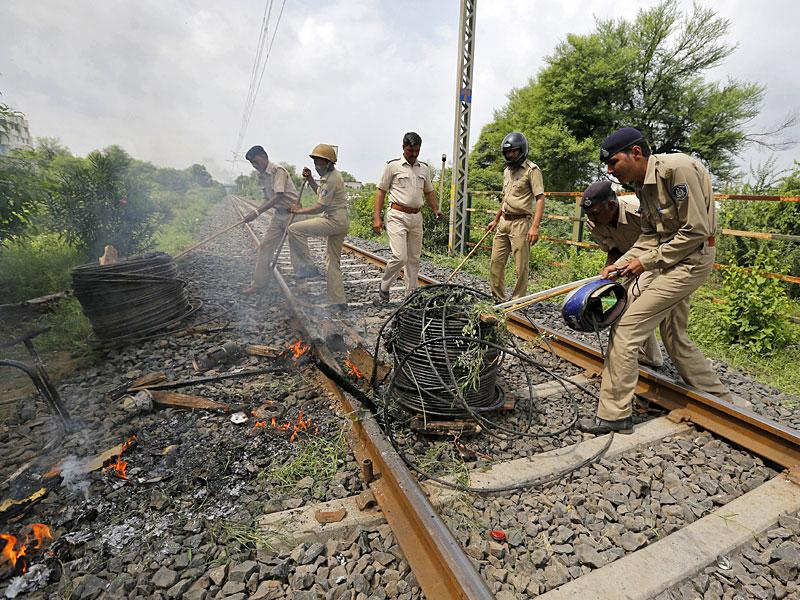 Policemen remove cables from a railway track which were set on fire by the protesters in Ahmedabad. India deployed paramilitary forces and imposed a curfew in the western state of Gujarat on Wednesday after violence broke out at a protest led by a powerful clan to demand more government jobs and college places. (Reuters Photo)