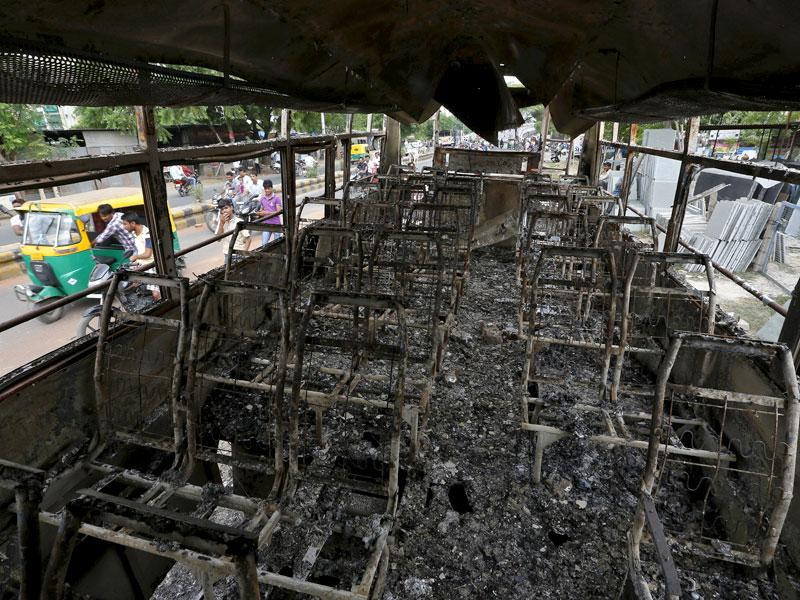 People are seen through a damaged bus that was burnt in the clashes between the police and protesters in Ahmedabad. Three people have reportedly died in widespread violence across Gujarat, with leader Hardik Patel vowing to intensify the agitation. (Reuters Photo)