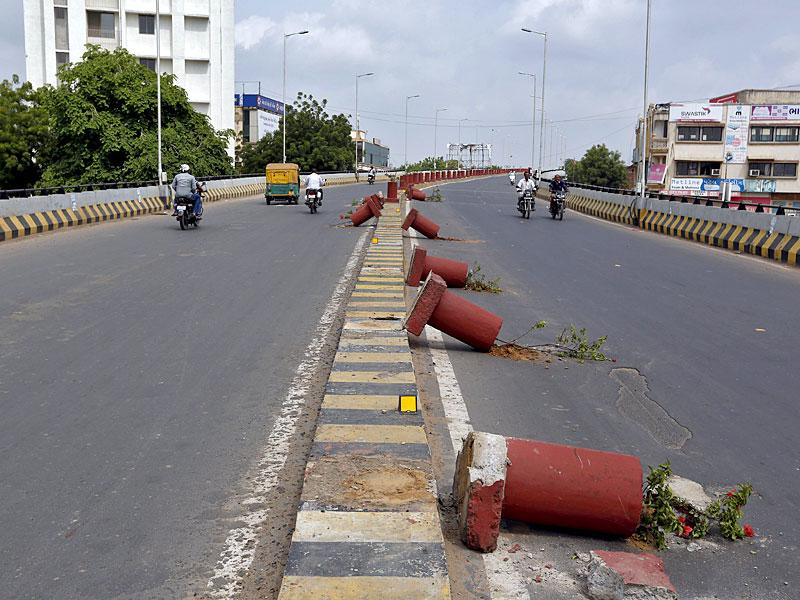 Vehicles travel past flower pots installed on a road divider which were damaged in the clashes between the police and protesters in Ahmedabad. Curfew was imposed in various parts of Gujarat as the Patidar community intensified its agitation. (Reuters Photo)