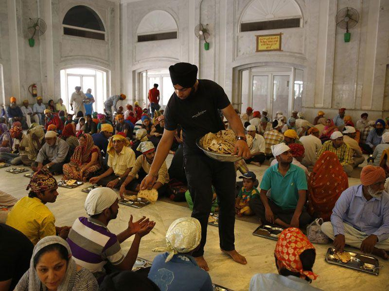 A business student takes time off his schedule to distribute food at a langar at the Bangla Sahib Gurudwara in New Delhi. (AP Photo/Manish Swarup)