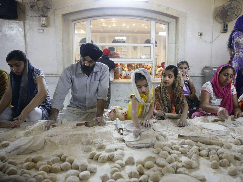 Service being of utmost importance to gurdwaras the devotees make Indian bread (aata) as they prepare langar at the Bangla Sahib Gurdwara in New Delhi. (AP Photo/Manish Swarup)