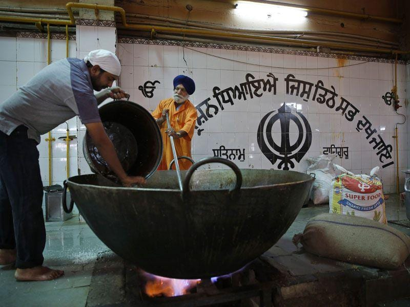 Two devotees in the kitchen of the gurdwara preparing delacacies for the langar at Bangla Sahib Gurdwara which feeds more than 10,000 everyday.(AP Photo/Manish Swarup)