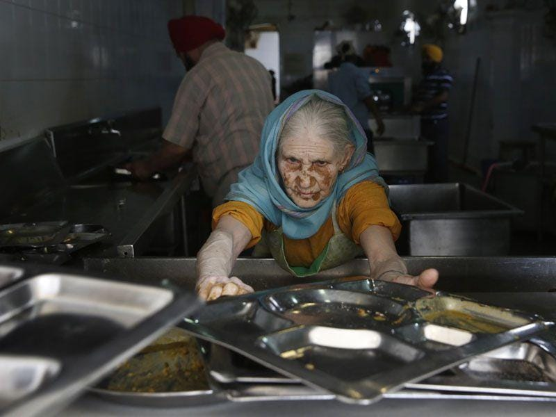 A woman collects used plates from devotees to clean after they finish eating langar at the Bangla Sahib Gurdwara in New Delhi.(AP Photo/Manish Swarup)