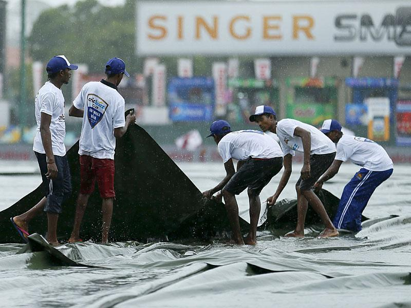 Ground workers pull the covers as play gets halted due to rain. (Reuters Photo)