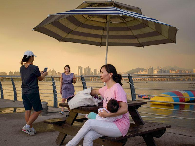 A woman cradles a child as she sits before the Han River and the city skyline in Seoul. (AFP Photo)