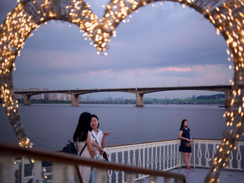 Passengers stand on the deck of a tour boat as it passes the city skyline along the Han River. (AFP Photo)