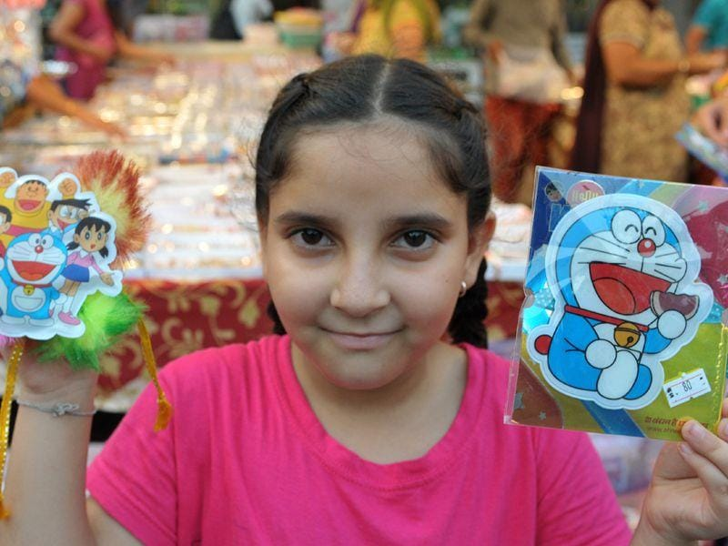 A girl holding up cartoon toys when out buying presents for her brothers. (Karun Sharma)