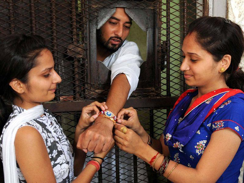 Two girls tying a Rakhi to their brother who is lodged at the Central Jail in Patiala. (Bharat Bhushan/HT)