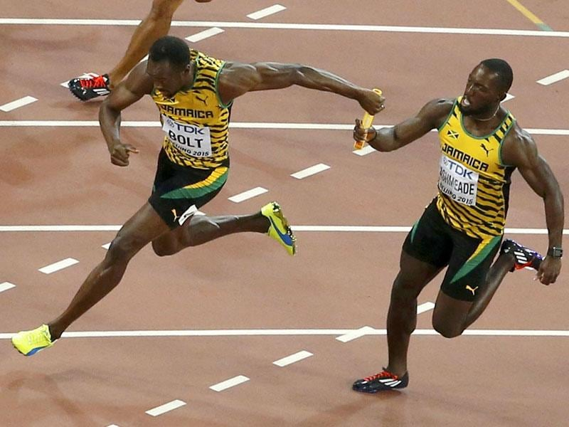 Bolt (L) receives the baton from teammate Nickel Ashmeade as they compete in the men's 4 x 100 metres relay. The world's fastest man made it 3 for 3 in Beijing again. (Reuters)