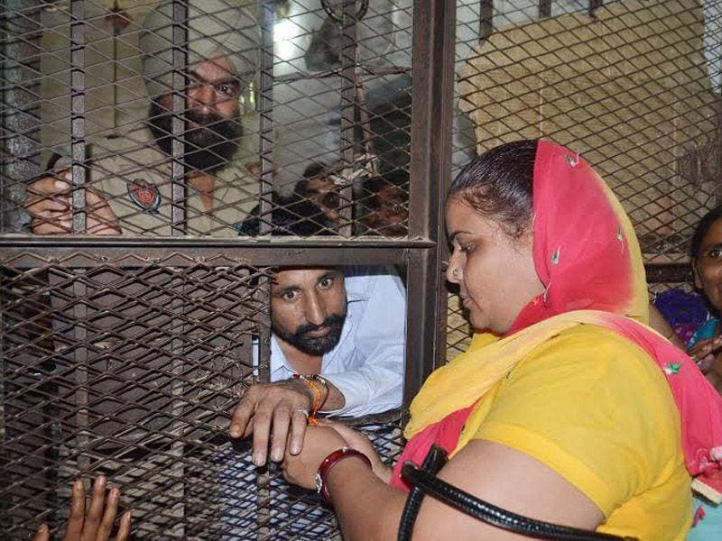 A woman tying rakhi to her brother at the Central Jail in Amritsar on Saturday. Sameer Sehgal/HT