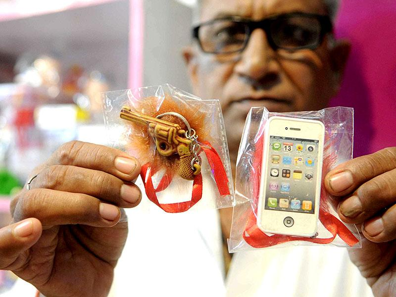 With the generations becoming trendy, rakhis are now available in various designs. Here's a shopkeeper shows rakhis designed as pistol and mobile phones as the latest trends (HT Photo/ Himanshu Vyas)