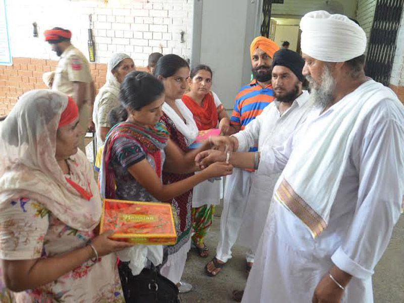 Women tying rakhi to their brothers at Central Jail in Amritsar on Saturday. Sameer Sehgal/HT